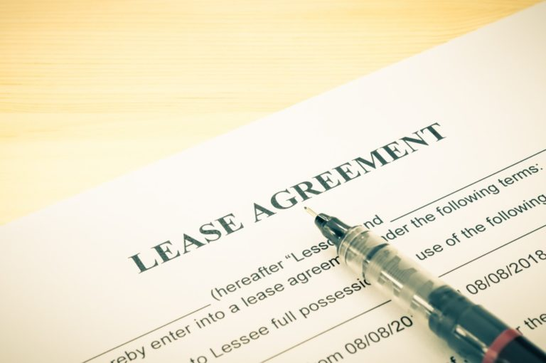lease agreement contract sheet and brown pen at bottom