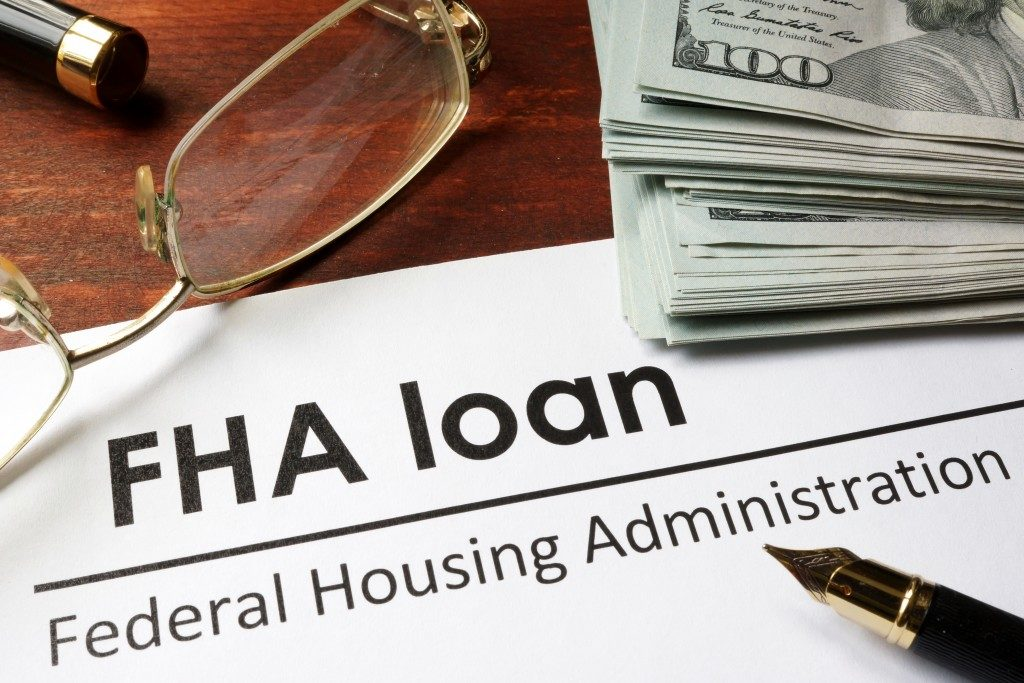 a fha loan document with a fountain pen and dollars on top of it