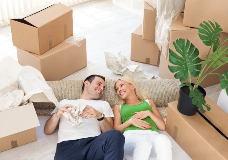 couple in between boxes smiling