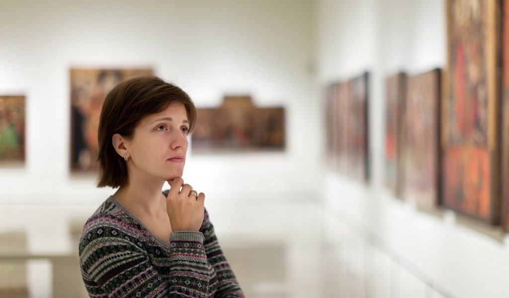 Woman looking at pictures in art gallery