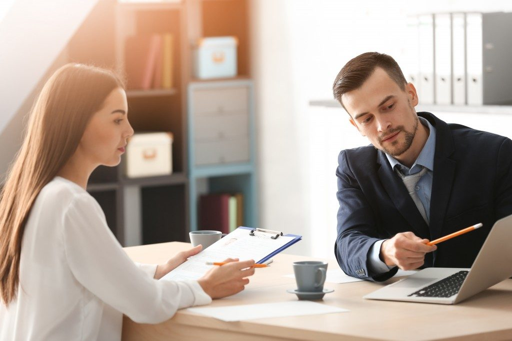HR manager interviewing young man in office